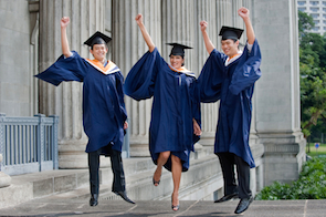 Three young graduates pump their fists in the air outdoors and celebrate their achievement