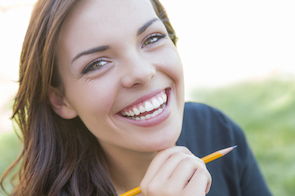 Portrait of Pretty Young Female Student with Pencil on Campus Lawn.